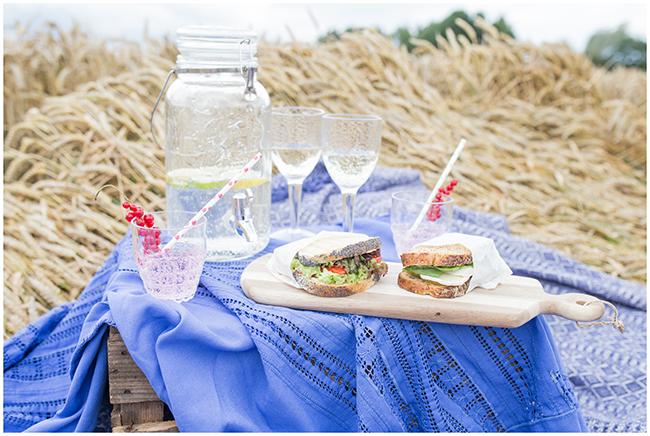 Weinkiste als Tisch beim Picknick im Kornfeld mit leckeren Sandwichideen auf dem Holzbrett