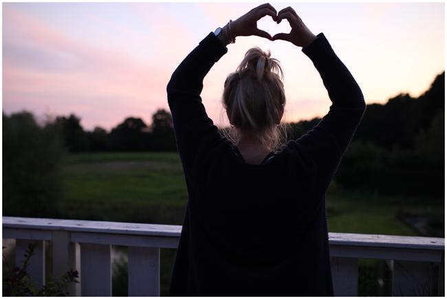 Selbstliebe – Ein Blick ins Grüne. Sonnenunterganz und die Hände zu einem Herz geformt.