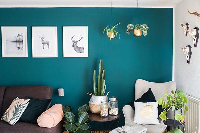 Wohnzimmergestaltung grüne Wand Pflanzen und Hirschbilder