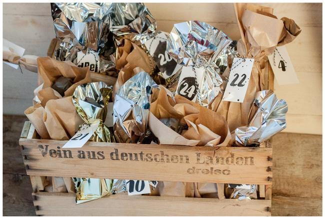 Ein gold und Silberfarbener Adventskalender in  der Weinkiste gefüllt mit Craftbeer für den Mann.