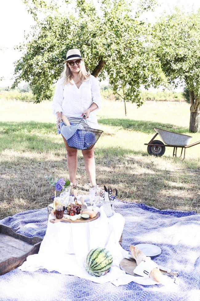 Ein Picknick im Schatten auf blauer Picknickdecke mit Crémant von der Loire und Baguette im Kartoffelsammelkorb